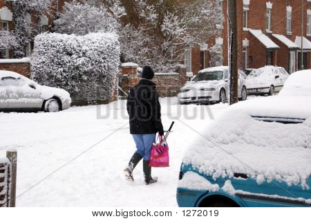 Woman Walking In The Snow Carrying A Bag