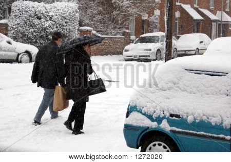 A Couple Walking In The Snow Carrying Bags