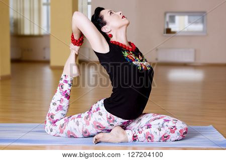 Young  Women Do Yoga Indoors, Pigeon Pose