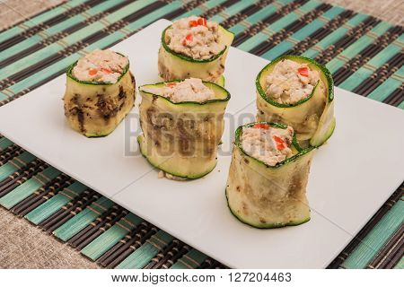 Grilled zucchini rolls with curd cheese and tuna on plate. Top view with copy space