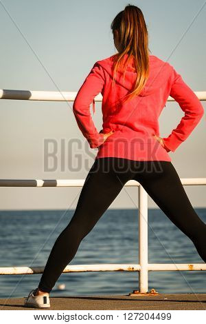 Woman Jogger Stretches On Pier By Seaside