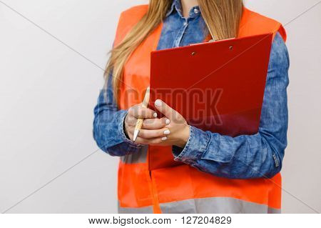 Woman construction worker builder structural engineerin in orange vest holds pen file pad. Safety in industrial work. Studio shot