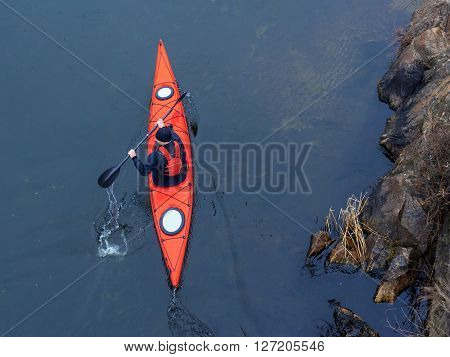 man paddles a red kayak on the river near the shore kayaking