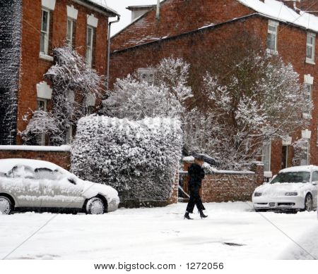 A Woman Walking In The Snow Carrying An Umbrella