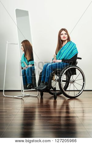 Real people disability and handicap concept. Teen girl handicapped woman sitting on wheelchair in front of mirror combing hair. Daily personal care