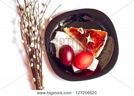Stylish black plate with piece of cake twigs of willow and Easter eggs isolated white background
