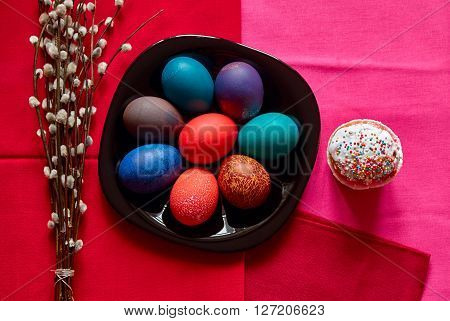 Festive Easter table in red colour with colorful eggs cake and willow twigs