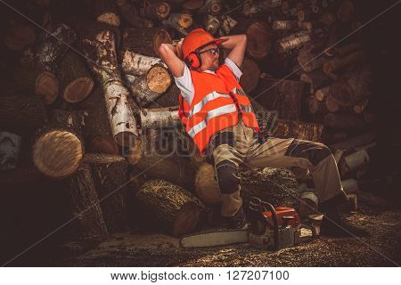 Lumber Wood Worker Break. Satisfied Lumber Worker Laying on the Pile of Wood Logs. Hard Work Satisfaction.