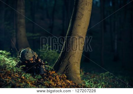 Military Night Time Operation. Army Soldier in the Dark Forest.