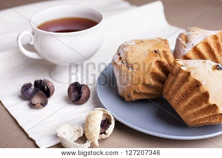 Muffin cakes and cup of tee on a grey plate. Beige - coffee background.