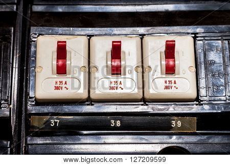 three old electric fuses with red switches