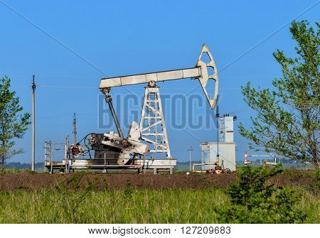 Old oil pumpjack on the summer field