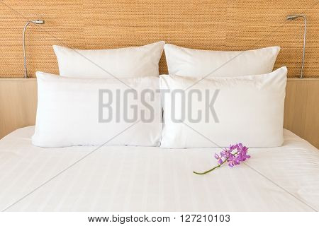 A White Bed With 4 Pillows And 2 Head Lights