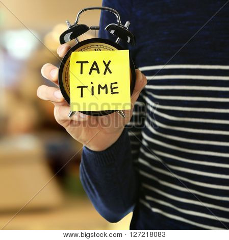 Tax concept. Man holding alarm clock, tax time
