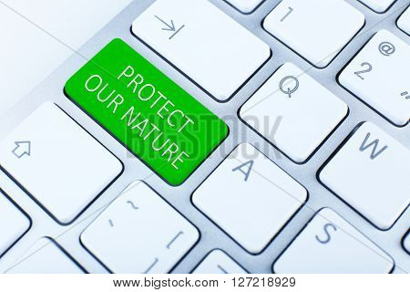 Close-up of laptop keyboard with color button and text Protect Our Nature
