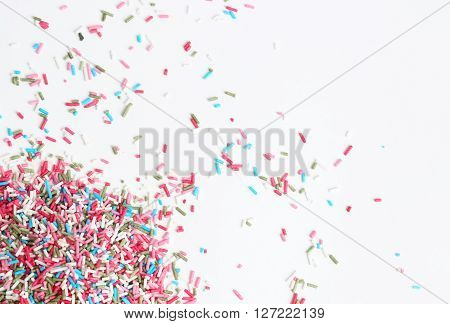 Colorful candy sprinkles on the white background -  top view