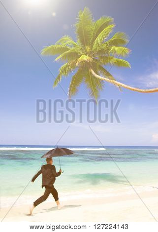 Businessman running at the beach.
