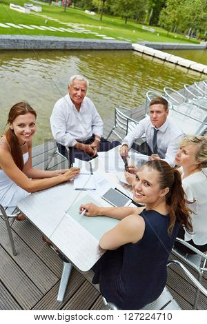 Business people having meeting outdoors on a table in a coffee shop