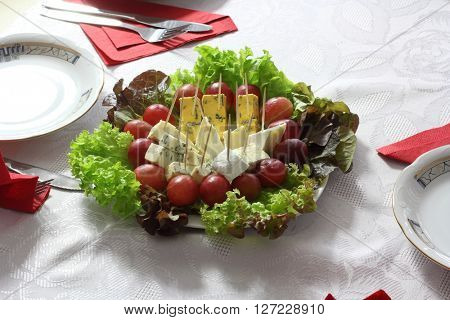 blue cheese close up with grapes and salad on table