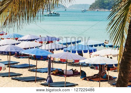 Phuket,Thailand - March 01, 2016: Parasol and some people relax on the white sand beach and blue sea with blue sky background