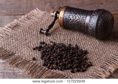 Black pepper corns and mill on wooden background