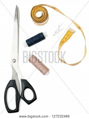 Tailors tools - scissors, spool of thread and tape measure on white. Top view