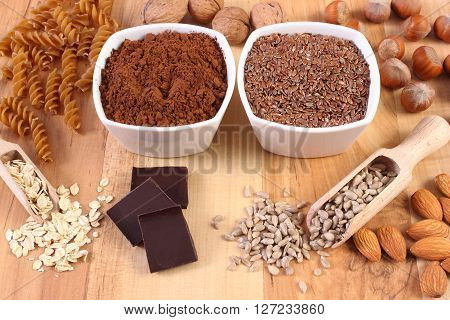 Fresh natural ingredients and products containing magnesium and dietary fiber healthy food and nutrition wholemeal pasta cocoa linseed hazelnut walnut oatmeal chocolate sunflower almonds