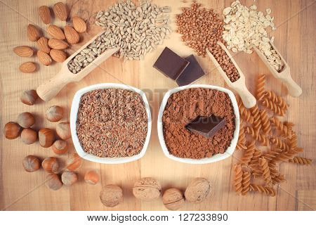 Vintage photo Fresh natural ingredients and products containing magnesium and dietary fiber healthy food and nutrition wholemeal pasta cocoa linseed hazelnut walnut oatmeal buckwheat chocolate sunflower almonds