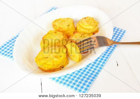 Baked potatoes with spices on a white plate, fork with a piece of potato