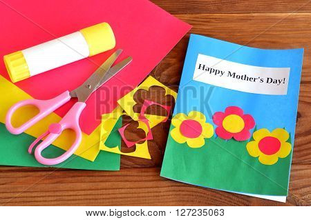 Greeting card Happy mother's day. Scissors, glue, paper scraps, paper sheets on brown wooden background