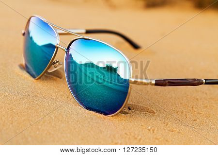Sunglasses on the sand summer desert is reflected in the glasses.