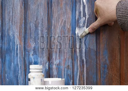 Male hand painting a wooden wall with a paintbrush outdoor shot with no people