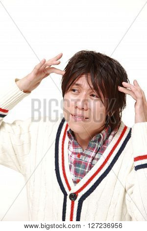 young Japanese man suffers from headache on white background
