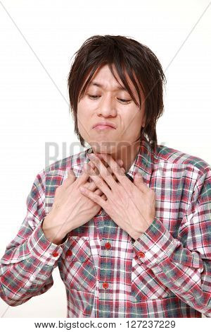 young Japanese man having throat pain on white background