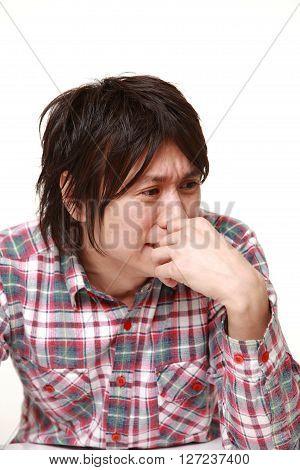 portrait of sad young Japanese man on white background