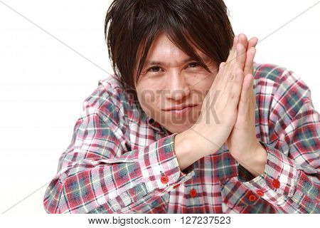 young Japanese man folding his hands in prayer