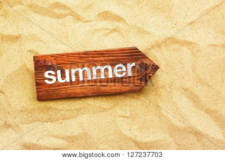 Summer direction sign in warm beach sand summertime holiday vacation top view