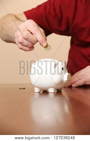 Senior man adding coin in his piggy bank
