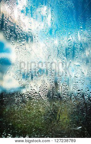 blue cloudy sky through wet glass