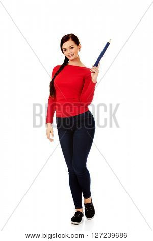 Beautiful student woman pointing up with a big pencil