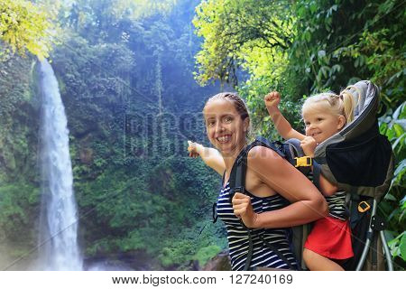 Mother hold baby girl on back in carrying backpack walking in waterfall canyon. Travel adventure and hiking activity with child active and healthy lifestyle on family summer vacation and weekend tour