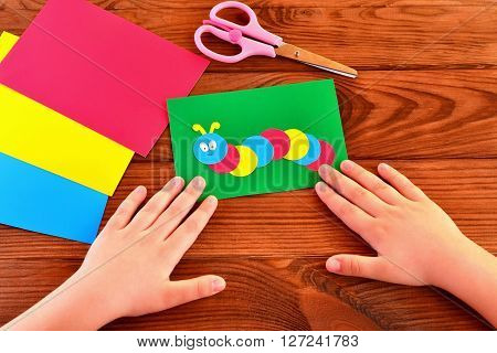 Children paper applique. Children hands, scissors, colorful paper sheets. Brown wooden background.
