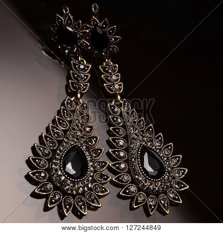 silver earrings with black stones on dark glass