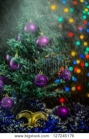 New year theme: Christmas tree white and silver decorations blue balls snow snowflakes serpentine and golden mask on white retro stylized wood background with yellow backlight