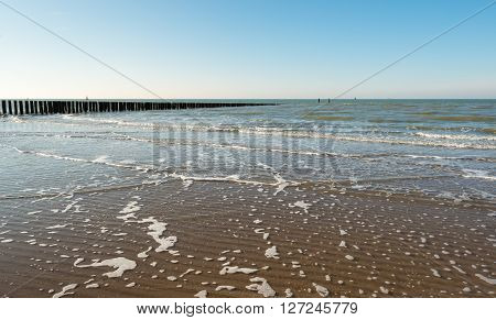 Closeup of the North Sea beach and the surf with foam on the water surface and waves in the sand. It's a sunny day in winter season.