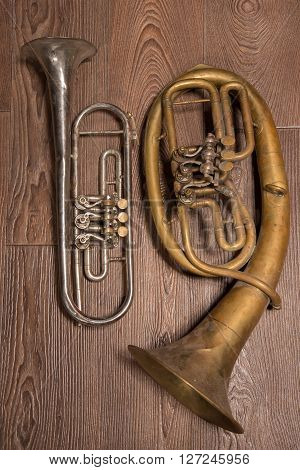 old brass wind instrument and horn on a wooden background. studio