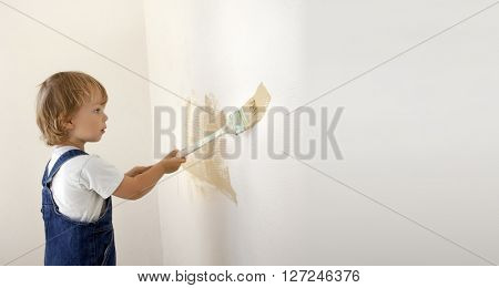 boy paints the wall roller