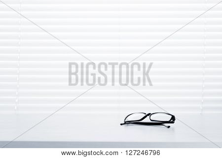 Office workplace with glasses on wood desk table in front of window with blinds. Toned