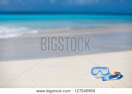 Snorkeling equipment mask and snorkel on tropical white sand beach