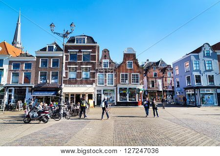 Delft, Netherlands - April 8, 2016: Colorful street view with traditional dutch houses on the square, bicycles, people walking in downtown of popular Holland destination